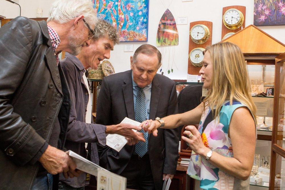 Gemma Baker and Larry Williamson show Mayor Ian Carpenter a wildflower inspired piece of jewellery.
