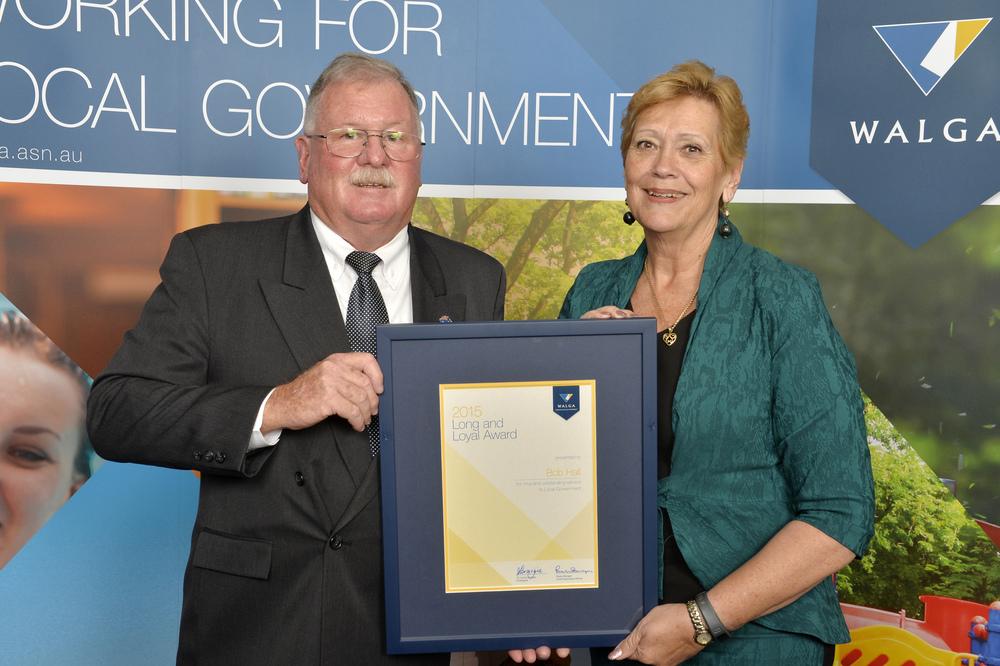 Councillor Bob Hall receives his Long and Loyal Service Award from WALGA President Lynne Craigie.