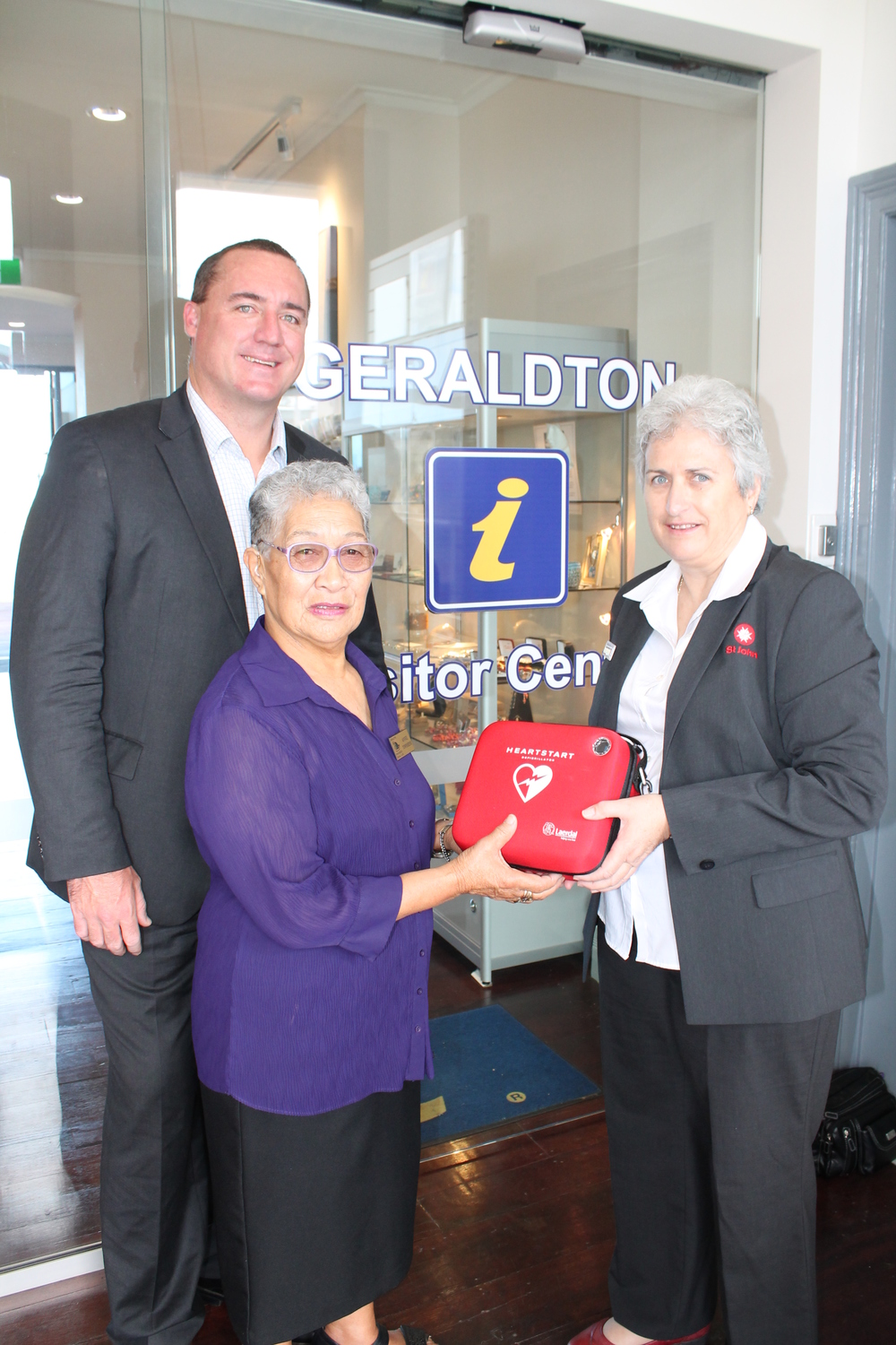 City of Greater Geraldton Mayor, Shane Van Styn, and Geraldton Pensioner Social Club President, Annie Smith-Townsend, receiving the Automated External Defibrillator from St John Ambulance Regional Manager Mid West, Lynne Hunt.