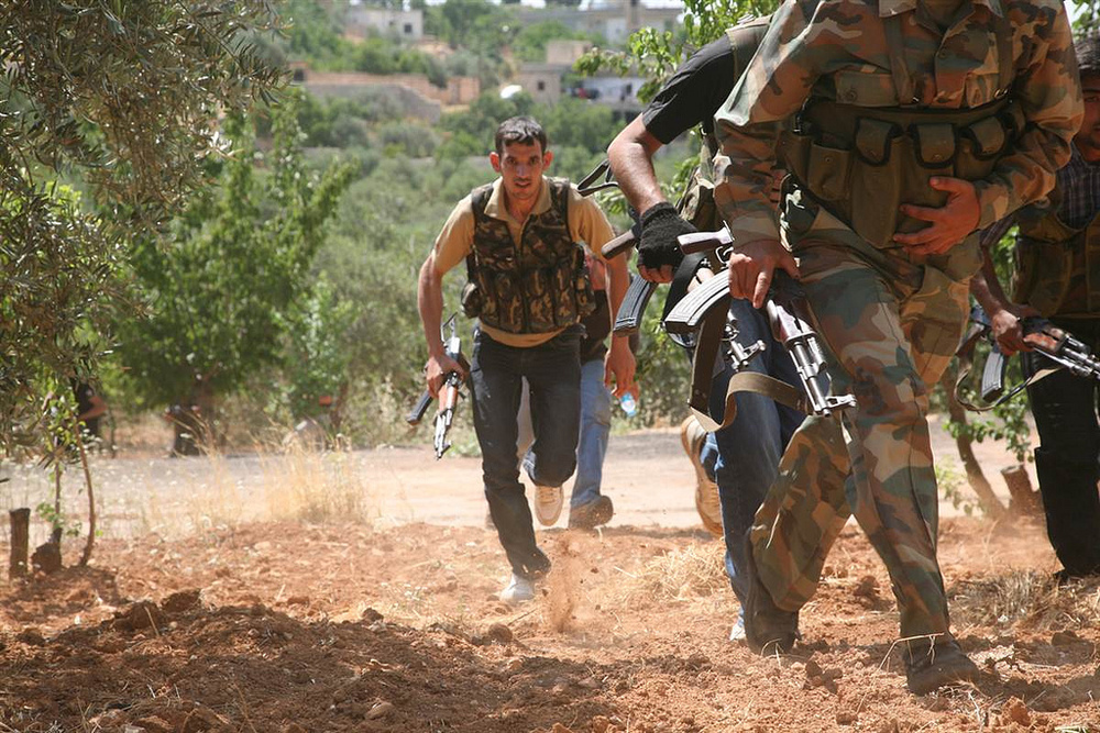 "Syrian   rebels from the ""Al-Qasas Brigade"" or ""Justice Brigade"" run through an olive grove to avoid Syrian Army snipers as they travel between villages on foot in the northwestern Jabal al-Zawiya area. Photo posted by Freedom House on 20 Oct 2012."