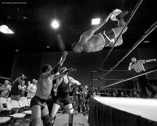 Keith Lee over the top rope against Mr. B and Thomas Shire. Photo by Joel Loeschman.