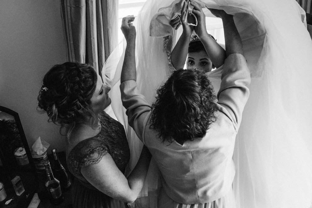 Bride getting helped into her dress