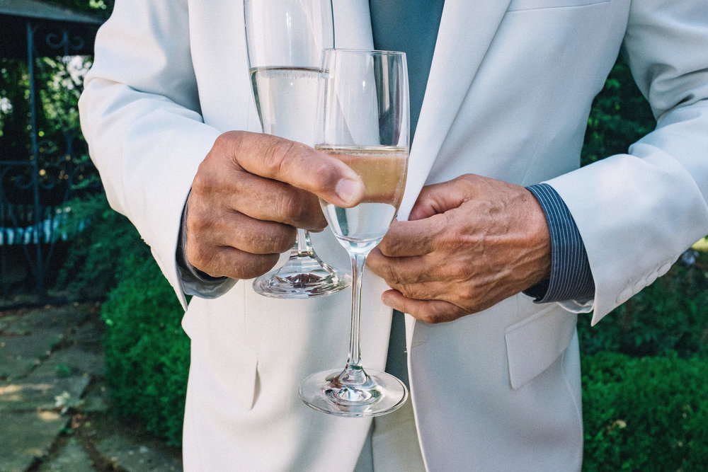 Groom's father unbuttoning his white jacket