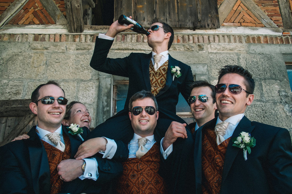 The groomsmen hold the groom on their shoulders The groomsmen hold the groom on their shoulders