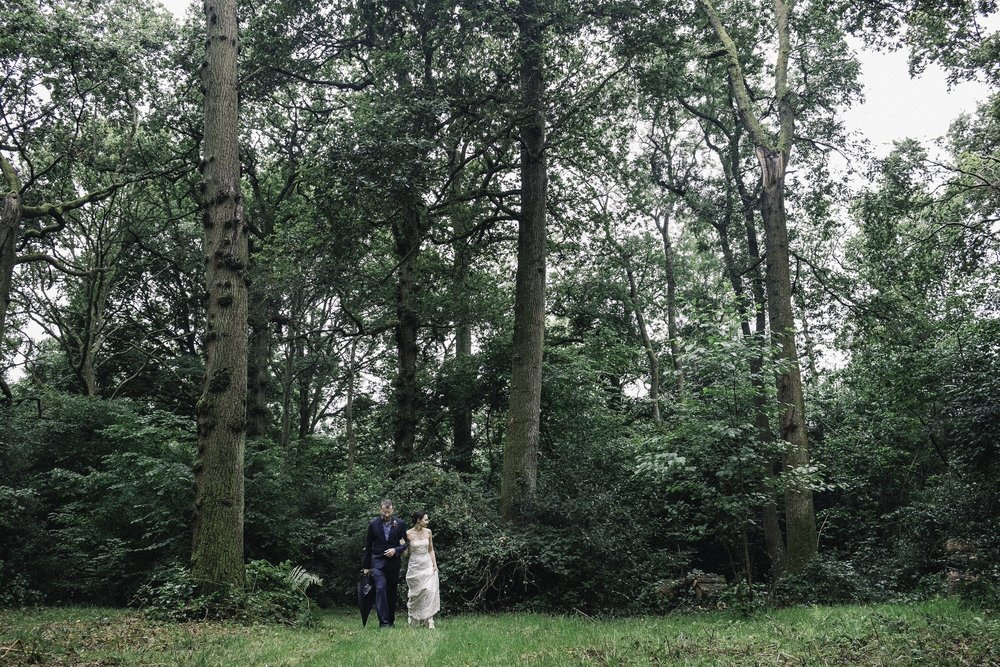 Bride + groom walking in forrest