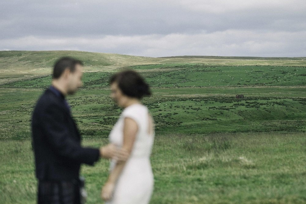 Bride & groom stand in a field