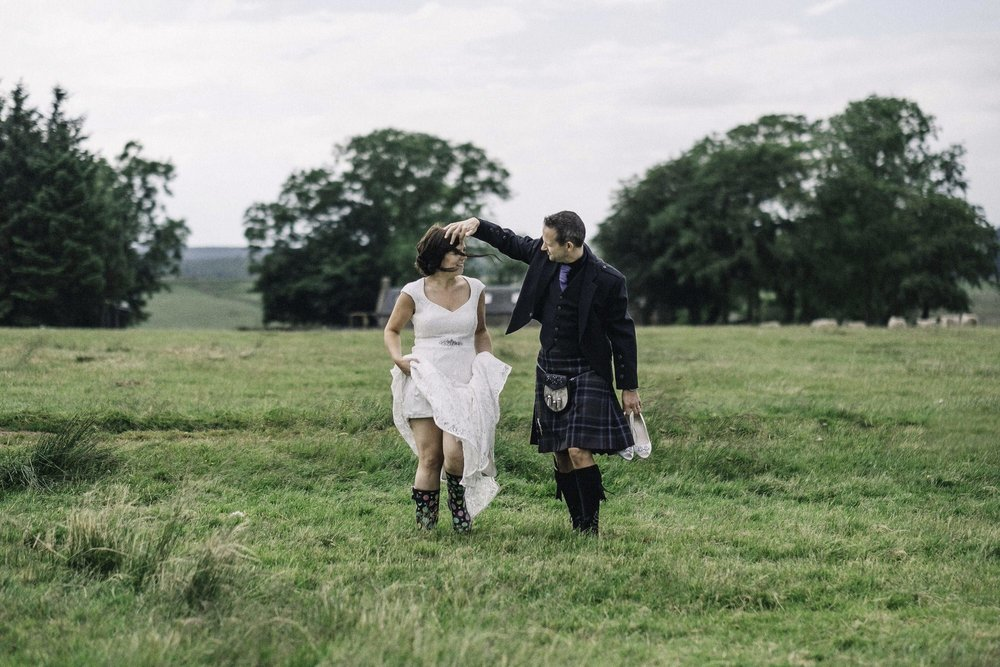 Bride & groom walking in a field