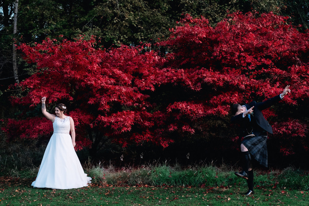 Bride and groom hold a dance move in front of a red bush
