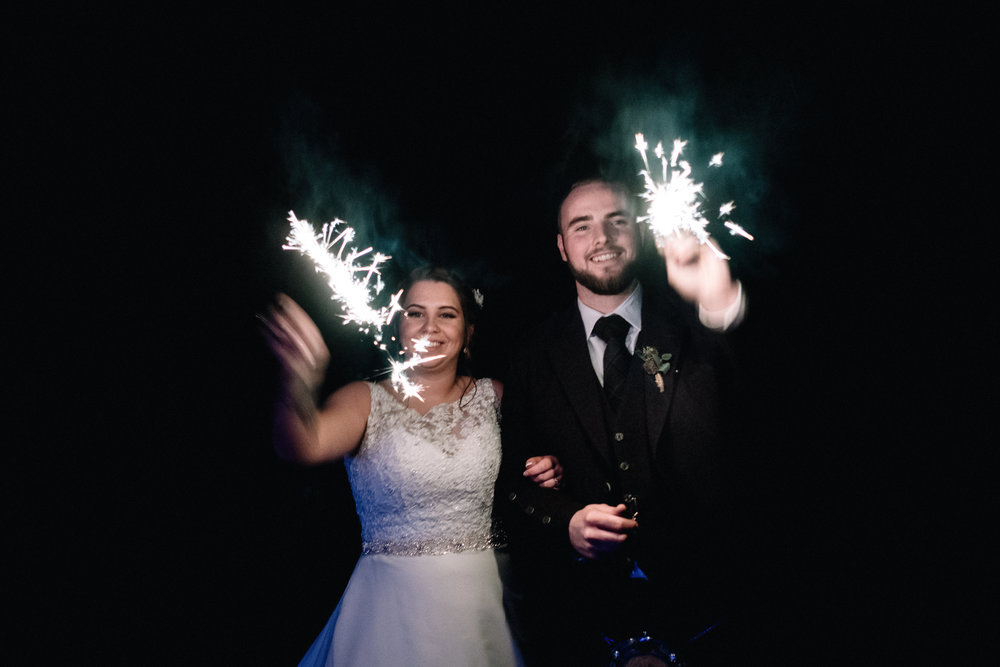 Bride and groom playing with sparklers