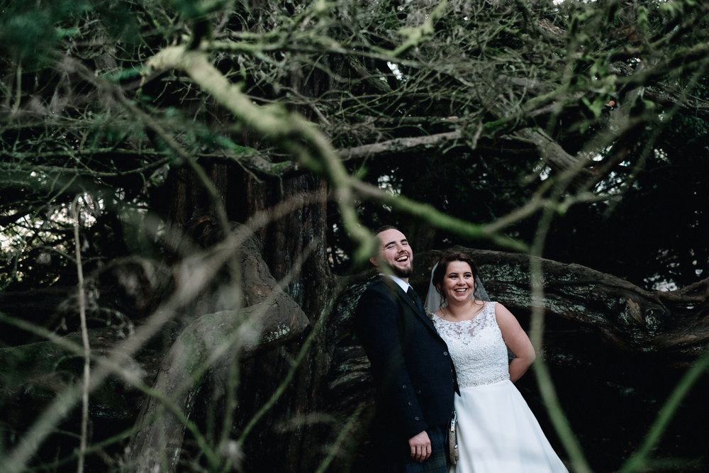 Laughing bride and groom in a forrest