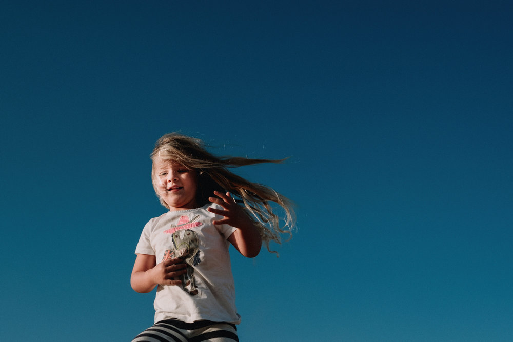 A young girl runs with blue skies behind her