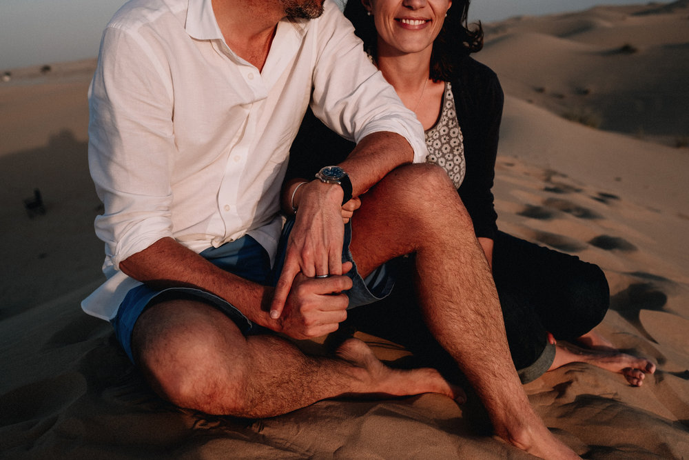 Couple sitting close together in the desert