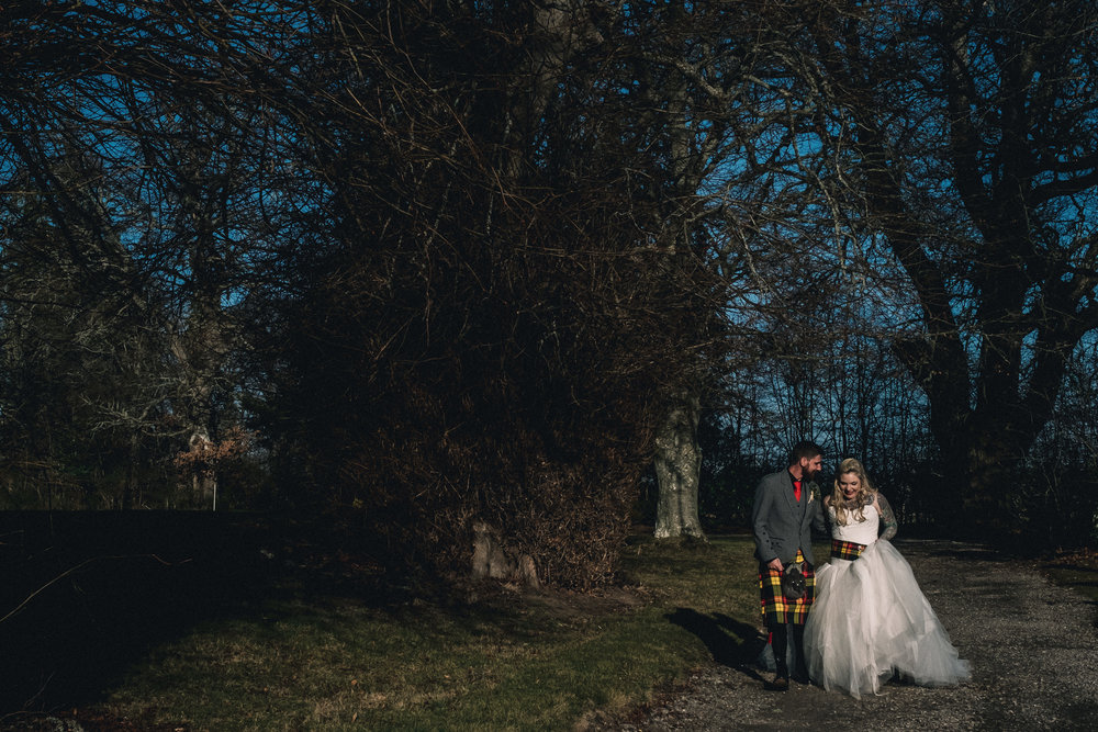 Bride and groom walk through trees