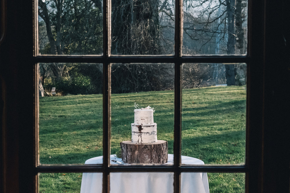 Wedding cake outside window on a table