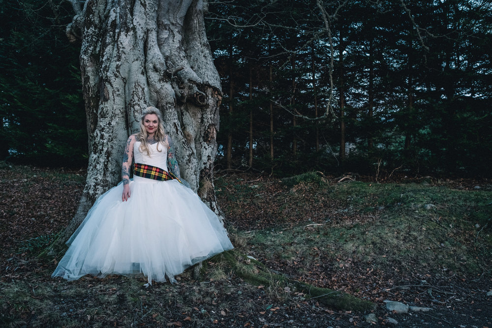 Bride leans on her own against a tree