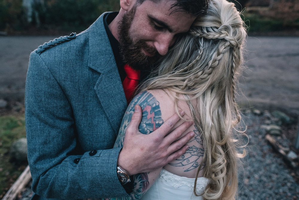 Groom holds his bride tightly in a warm embrace