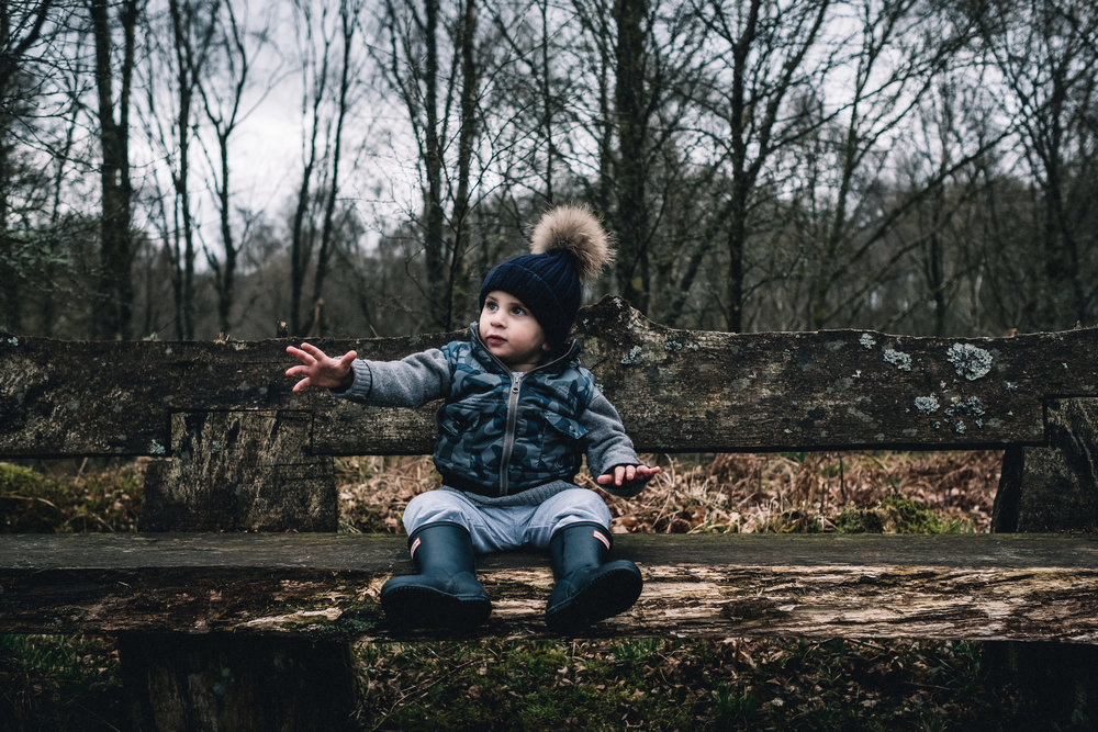 Child sits on a bench in a forrest