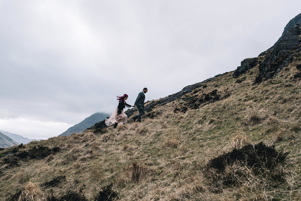 Bride + groom walk on mountainside