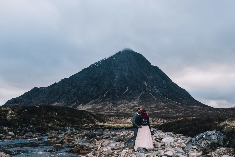 A couple stand at the foot of Buchaille Etive Mor