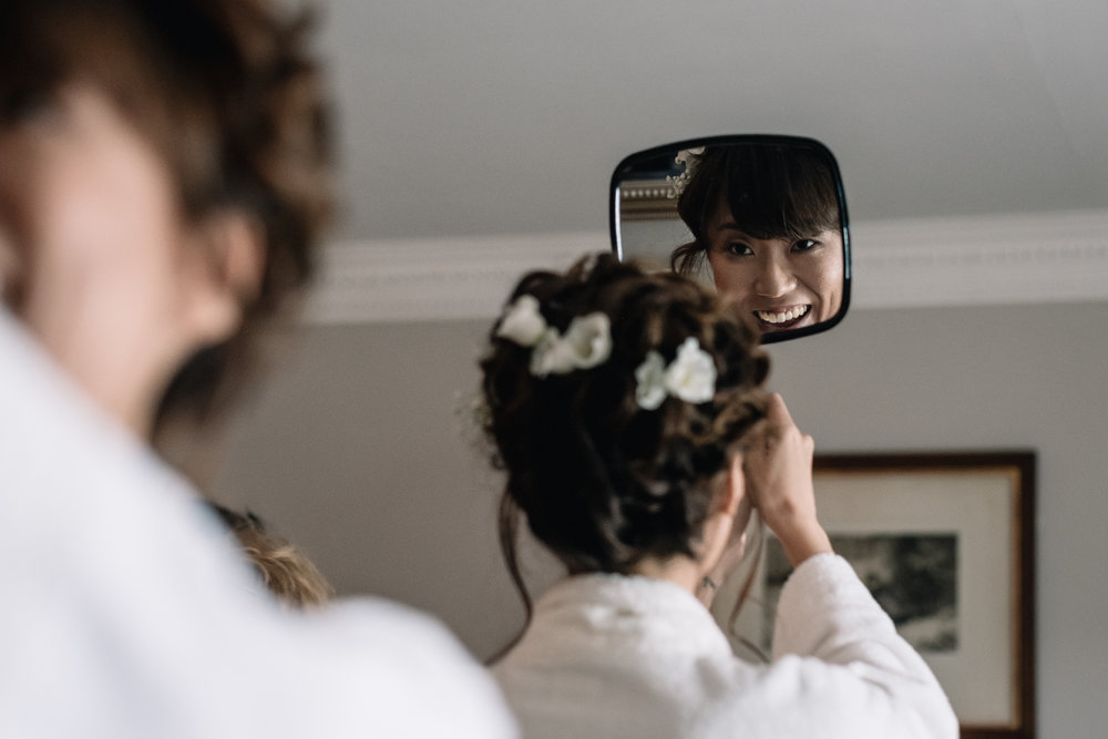 Bride checks hair in hand held mirror