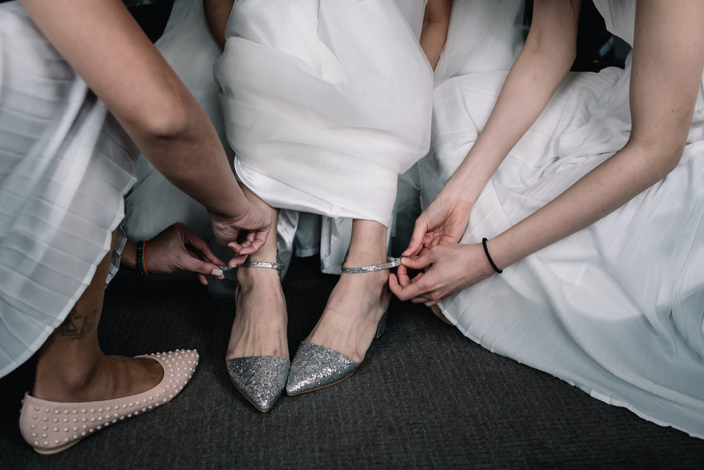 Silver weddings shoes being placed on bride