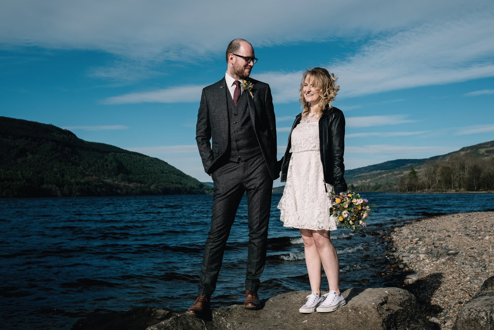 Married couple stand on rock by Loch Tay