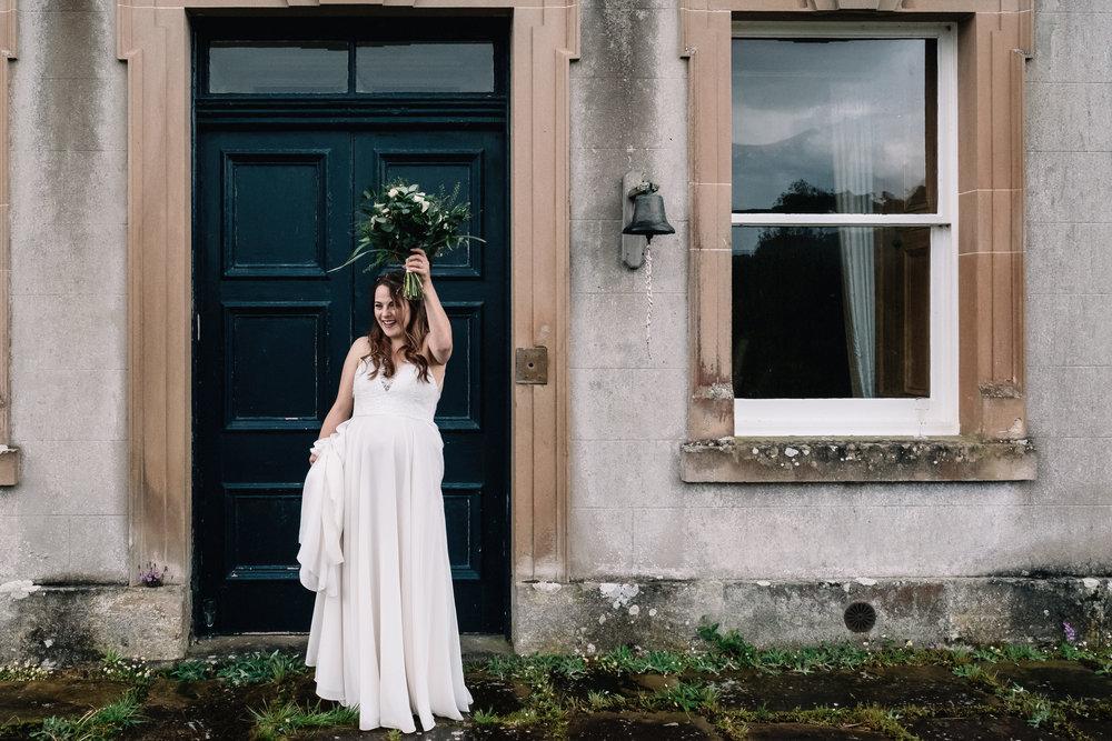 Bride holding her bouquet aloft