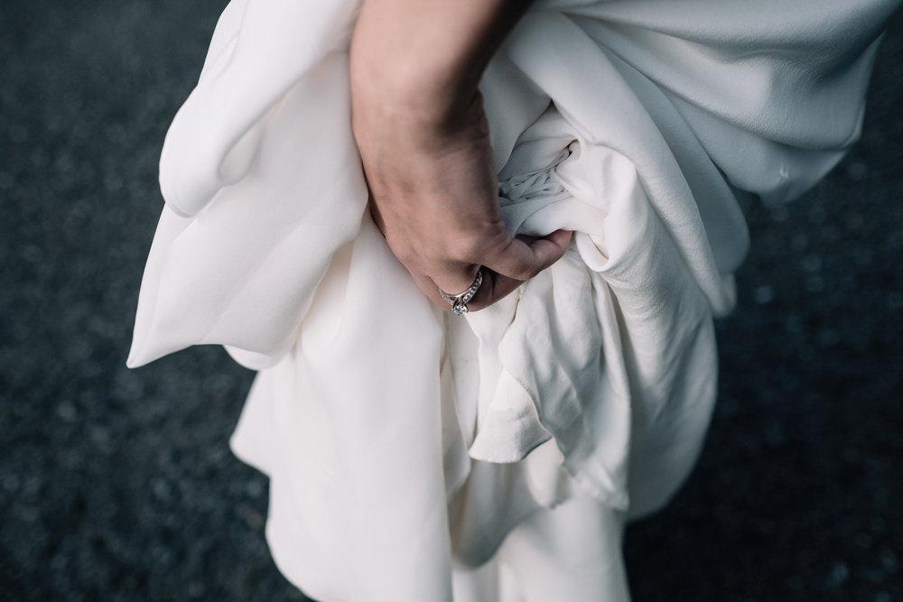 Bride holds her dress from Rue de Seine