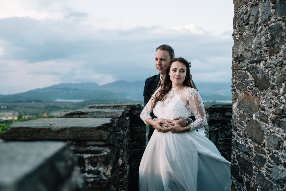 Bride and groom stand up watch tower of Lochnell Castle