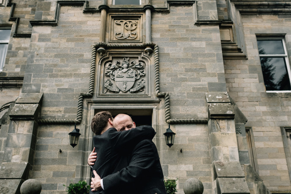 Embrace between groom and best man