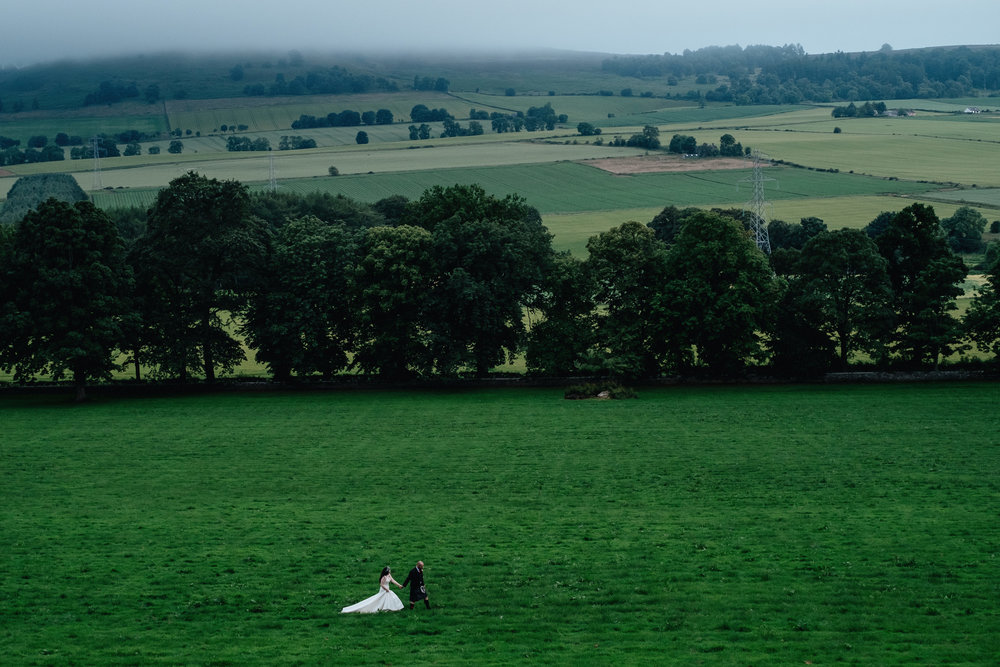 Bride and groom walk in field holding hands