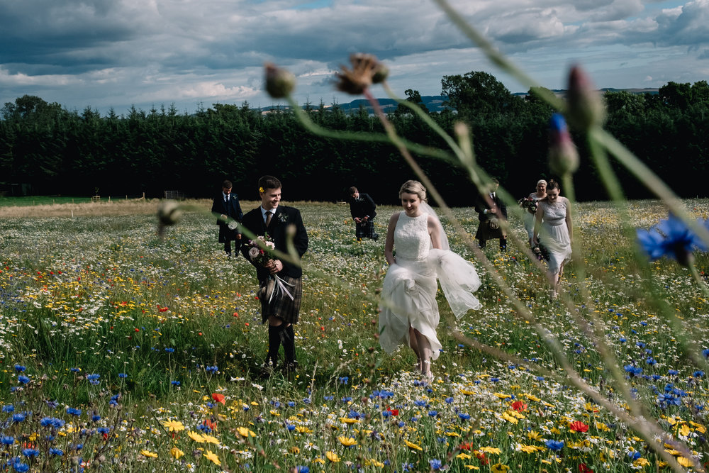 Bridal party walk in field of wild flowers