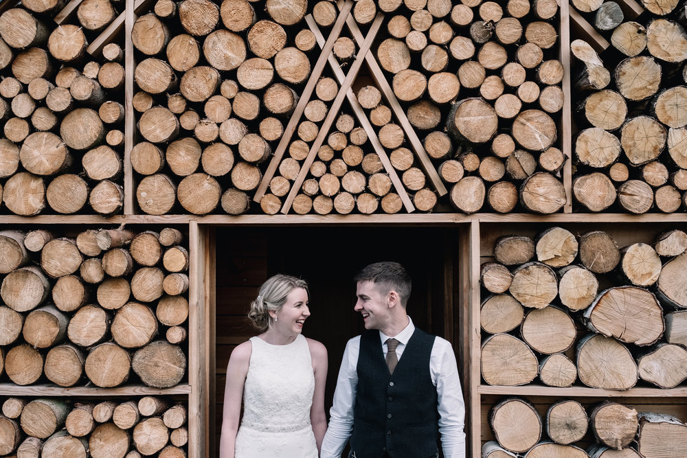 Bride and groom standing at log cabin