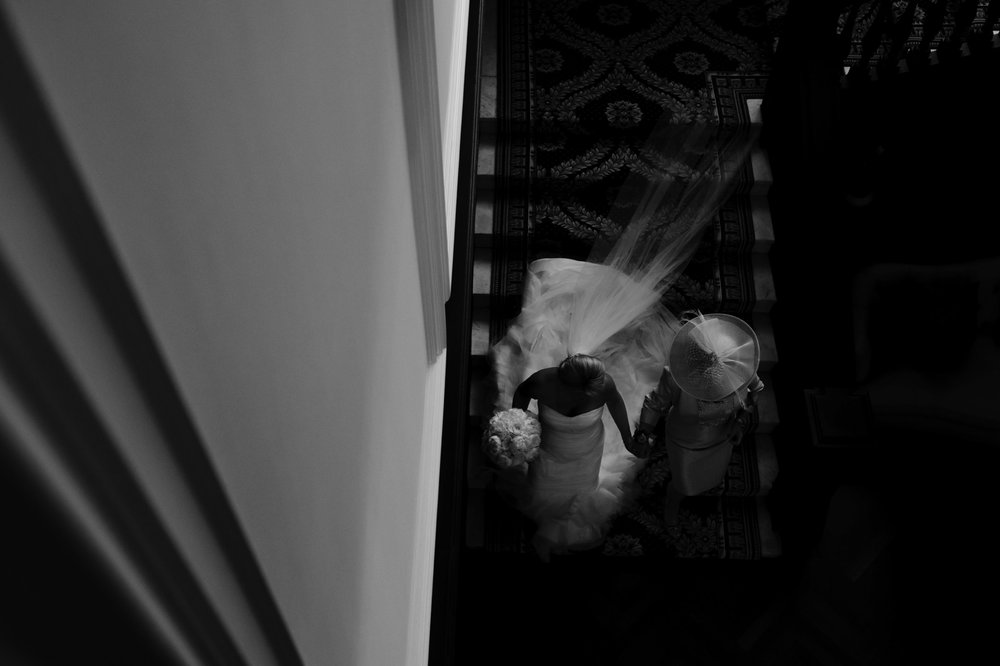 Bride and mother walk down staircase