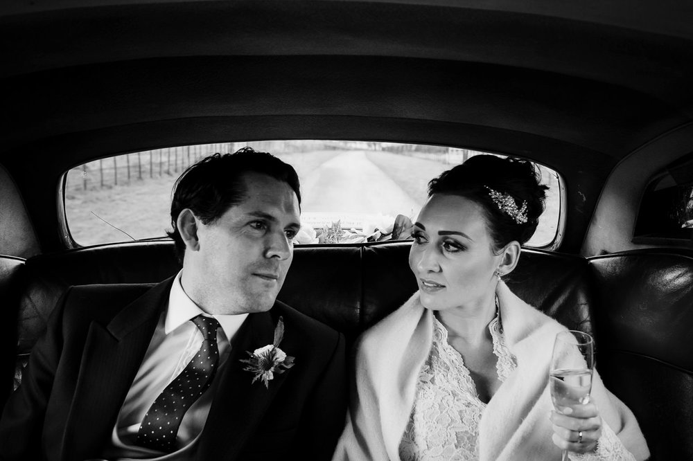 Couple sit in back seat of Bentley on a winter wedding day