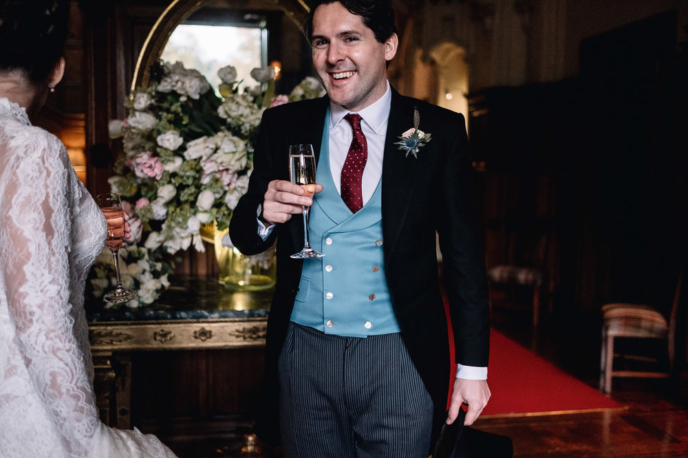 smilng groom holds his Champagne glass