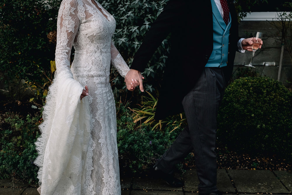 close up of bride and groom holding hands as they walk