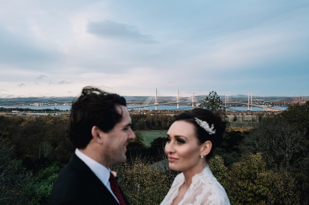the two bridges are in focus from the rooftop of Dundas Castle's keep on their wedding day