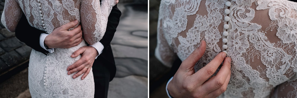 close up of groom's hands which are holding the back of his bride's lace dress