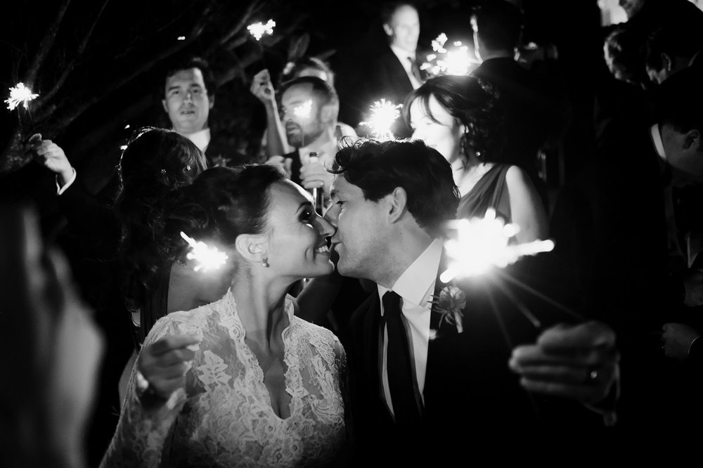 bride and groom kiss as they hold their sparklers away from themselves towards the camera surrounded by their bridal party