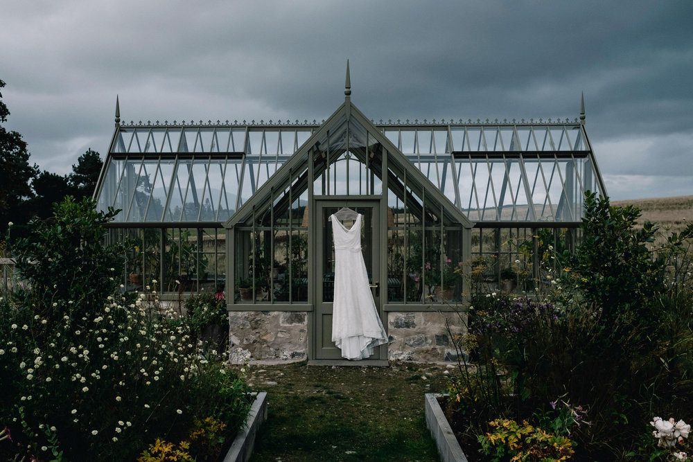 Wedding dress hangs from greenhouse on Killiehuntly Farmhouse.