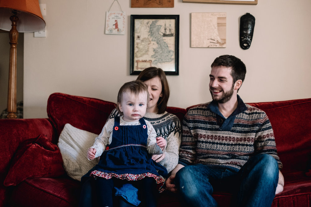 Mother, father and daughter sit on sofa in their living room in Fife.