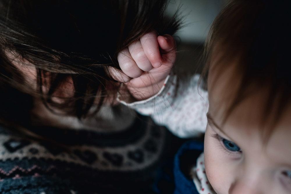 Little girl grabbing hold of her mother's hair.