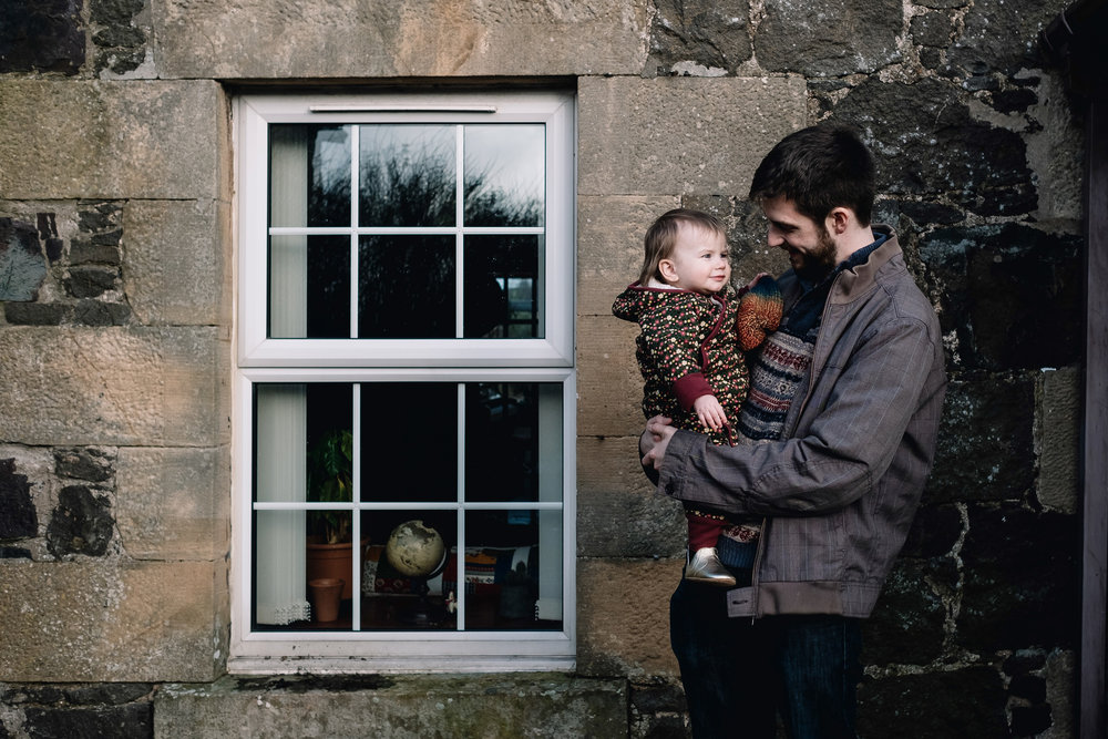 Father and daughter stand outside their house. He is holding her and looking at her.