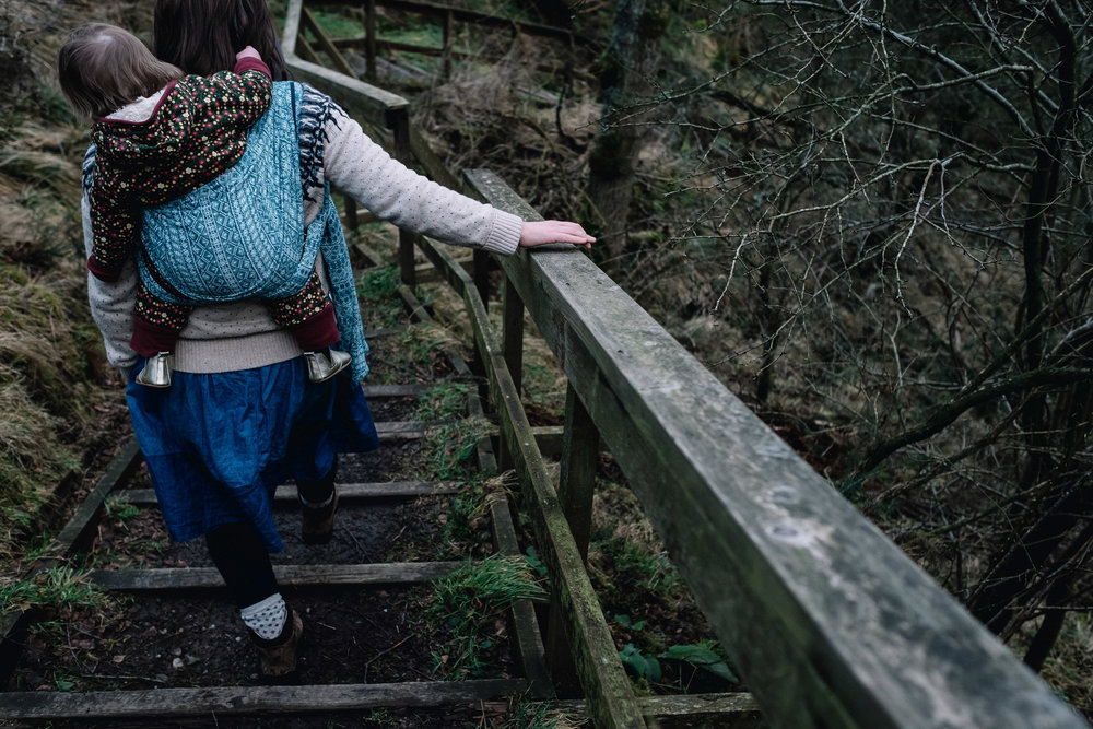 Mother holds onto wooden beam as she walks in a forrest.