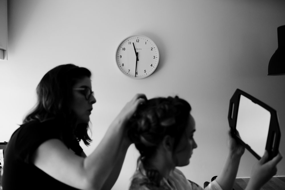 Bride holds mirror to check out her hair