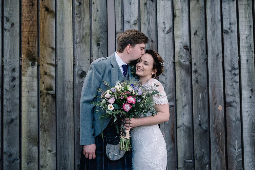 Groom places a kiss on bride's forehear