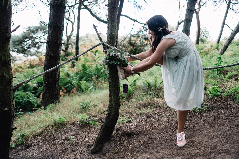 Bridesmaid leans over to tighten shoe lace before heading down a steep hill