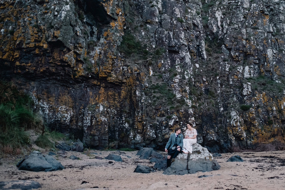 Bride and groom sit on a rock at the beach at the bottom of the log cabin.