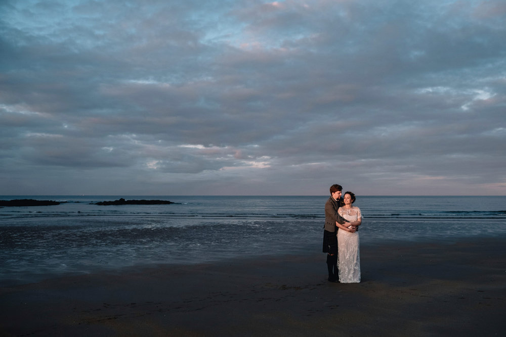 A newly married couple stand on the beach at sunset at th elog cabin at Ravensheugh.
